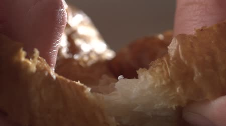 croissants : Close-up of a girls hands breaks a fresh croissant, slow motion. Fresh sweet pastries, close-up Stock Footage