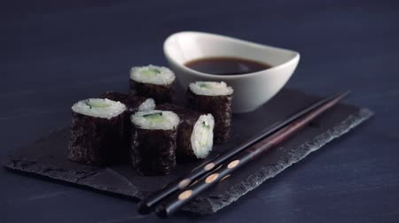various tea : Japanese restaurant, sushi roll on black slate plate. Set for one person with chopsticks, ginger, soy