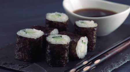 california rolls : Japanese restaurant, sushi roll on black slate plate. Set for one person with chopsticks, ginger, soy