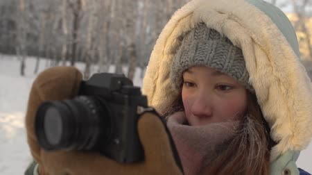 knitted gloves : Beautiful young woman in winter clothing, mittens and wool hat photographing snowy forest by a knitted camera