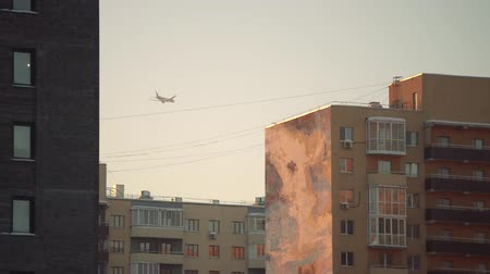 фюзеляж : Airplane in a golden sky with modern buildings.