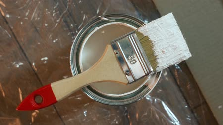 Painter brush and white paint tin macro over wooden pattern background. Stok Video