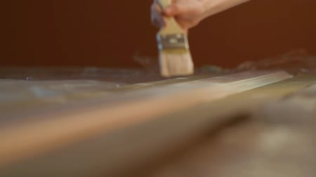 Close-up video of girls hand with a brush painting wooden desk