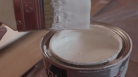 can : Hand of painter dipping a brush into a bucket with white paint , slow motion.