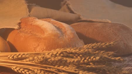 handmade tasty bread lying on burlap on the wooden table with flour, wheat and ears of wheat. Stok Video