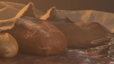 pékség : handmade tasty bread lying on burlap on the wooden table with flour, wheat and ears of wheat. Stock mozgókép