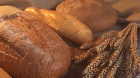 boş : handmade tasty bread lying on burlap on the wooden table with flour, wheat and ears of wheat. Stok Video