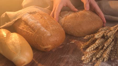 Closeup of male hands put fresh bread on an old rustic table with wheat. Stok Video