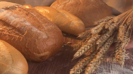 Closeup of male hands put wheat on an old rustic table with fresh bread.