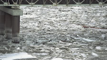 veszélyes : Frozen ice river is melting in spring with ice flakes flowing. Cracked ice floating on the river in spring time. Global warming