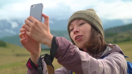 make photo : A young woman makes selfie on the mountains. A pretty lovely asain tourist girl take a selfie photo by using mobile smart phone high hill background.