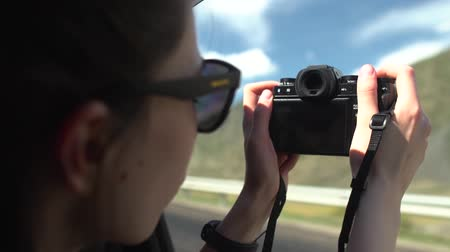 beautiful asian girl in black sunglasses taking photos of mountains with vintage camera on road trip in convertible car. Stok Video