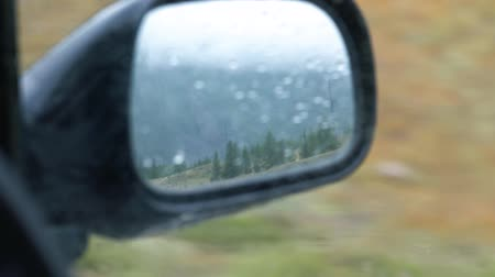 bruk : Driving mirror reflecting travel road in the rear with rainy mountains background.