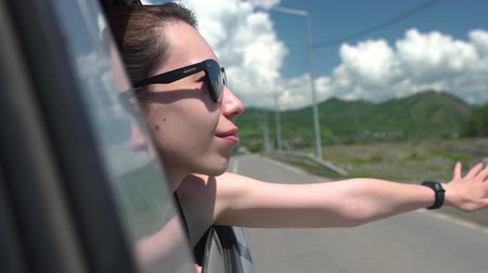 se movendo para cima : Happy girl in sunglasses leaning out of car window and enjoying trip in mountains. Young woman looking out window of moving auto on sunny day. Travel and freedom concept. Slow motion Close up.