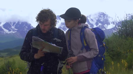 Couple standing on a mountain path looking at a map while standing on a mountain path Stok Video
