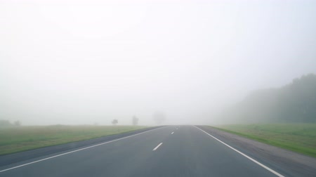 escorregadio : Cars on the road in the fog. Bad weather and dangerous automobile traffic on the road. Light vehicles in fog. Foggy gray road, cars driving fading into the fog