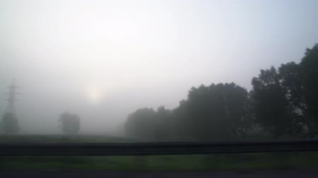 ahead : Cars on the road in the fog. Bad weather and dangerous automobile traffic on the road. Light vehicles in fog. Foggy gray road, cars driving fading into the fog