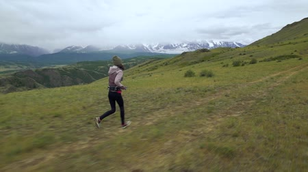 Trail running young women in cross country run. Girl runners training jogging outdoors in beautiful mountain nature landscape on white snowy peak at background