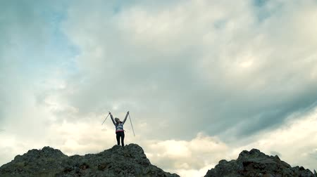 torcendo : Back view of excited hipster girl standing on high mountain top feeling free raising hands up, happy female traveler with backpack celebrating achievement of reaching peak during hiking tour