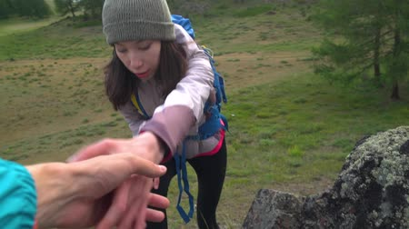The rock climber gives hand for help to the partner