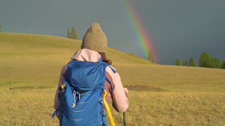 Woman hiking. Hike in the mountains. Woman traveler with backpack on beautiful summer landscape. A girl walking in the mountains goes to the rainbow