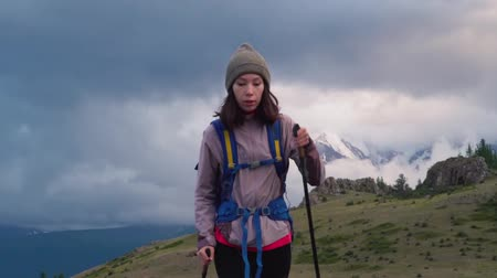 A girl with a backpack and trekking sticks travels in the mountains. The valley, with low clouds covering the snow-capped mountains.. Hiker trekking or walking of footpath. Healthy fitness lifestyle outdoors