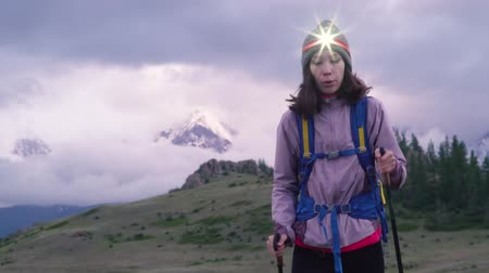 A girl with a backpack, a headlamp and trekking sticks travels in the mountains in the evening. The valley, with low clouds covering the snow-capped mountains.. Hiker trekking or walking of footpath. Healthy fitness lifestyle outdoors