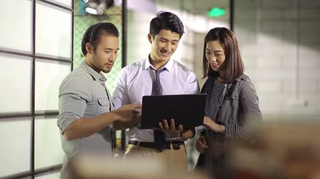 casual wear businessman : three young asian entrepreneurs discussing business using laptop computer in office. Stock Footage