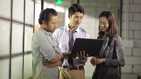 casual wear businessman : small group of young asian entrepreneurs discussing business using laptop computer in office.