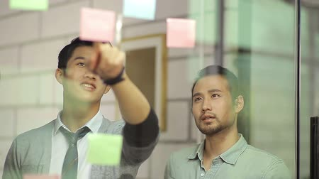estratégico : Asian corporate executives discussing business using sticky notes in office. Stock Footage
