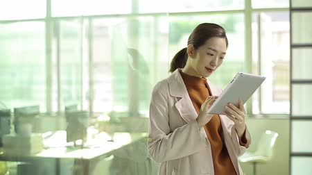 szingapúr : young asian business woman using digital tablet in office. Stock mozgókép