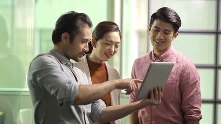 discussão : team of young asian business executives working together using digital tablet in office.