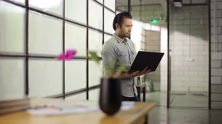 casual wear businessman : young asian businessman holding laptop computer thinking in office. Stock Footage
