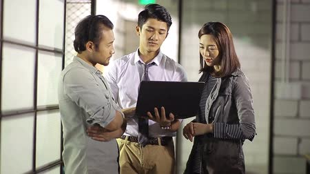casual wear businessman : Asian corporate executives discussing business using laptop computer in office.
