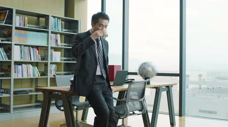 contemplativo : successful asian businessman sitting on desk drinking coffee and thinking