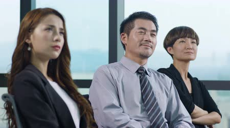approving : asian corporate executives listening to speech or presentation.