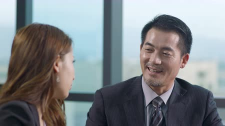 appraisal : asian business man and woman talking in office. Stock Footage