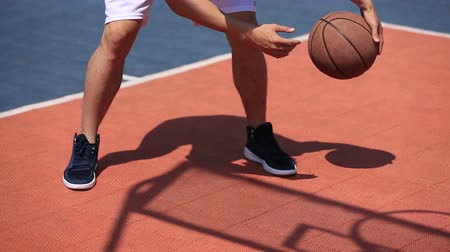 singapur : young asian basketball player practicing bouncing and dribbling the ball. Stok Video