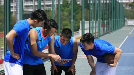 taktika : group of asian young adult basketball players discussing tactics using digital tablet. Dostupné videozáznamy