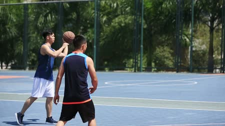 defending : young asian adults playing basketball on outdoor court, high angle view