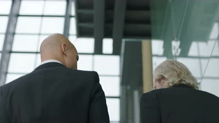 western wear : two corporate executives discussing business while descending stairs in modern company. Stock Footage
