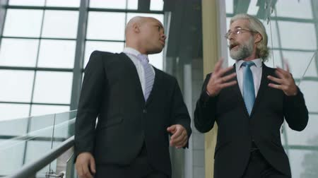 western wear : two businessmen descending stairs in modern company with glass structure. Stock Footage
