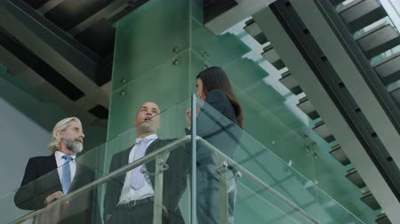 western wear : three corporate executives standing on second floor of a modern glass and steel building discussing business. Stock Footage