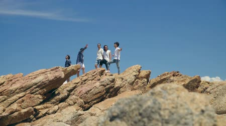 korejština : group of five young asian adults standing on top of rocks by the sea. Dostupné videozáznamy
