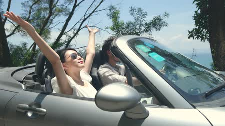 singaporean : young asian couple having fun driving and riding in convertible sport car on seaside road?