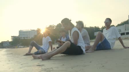 musician : group of five young asian adult men sitting on beach relaxing singing playing guitar, slow motion.