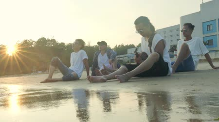 attitude : group of five young asian adult men sitting on beach relaxing singing playing guitar, slow motion.