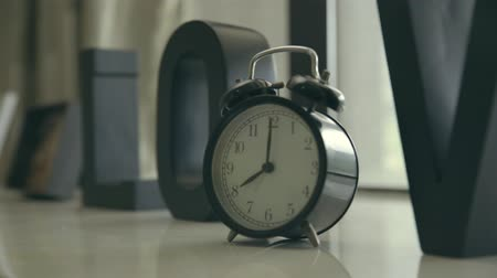 pan shot : alarm clock on table showing eight oclock, close-up.