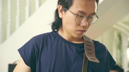 singaporean : young asian man musician male guitarist ready to play guitar.