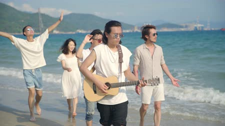 guitarrista : group of young asian adults men and women having fun walking singing on beach